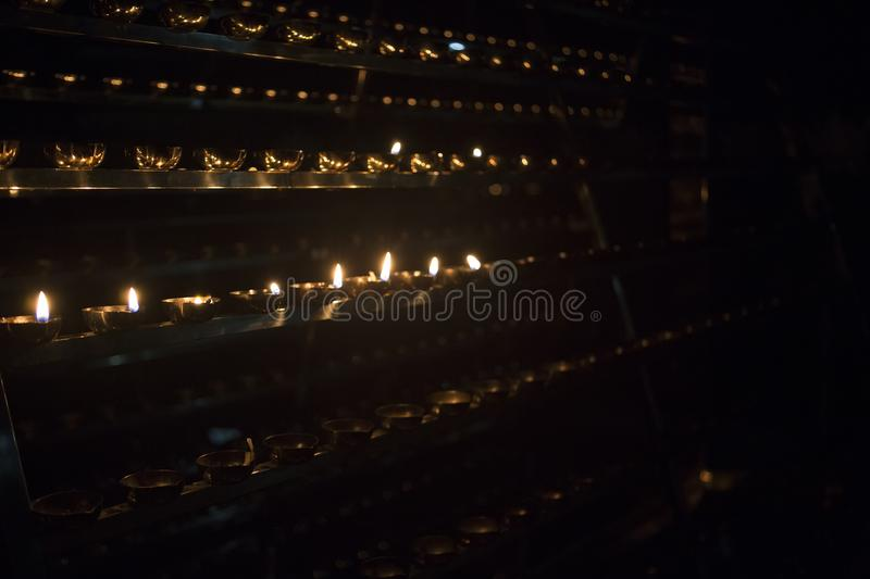 Candle flame close-up. Many Candles in a Buddhist temple. Religious Festival. Oil Lamp stock images