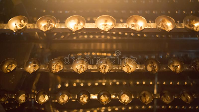 Candle flame close-up. Many Candles in a Buddhist temple. Religious Festival. Oil Lamp royalty free stock photography