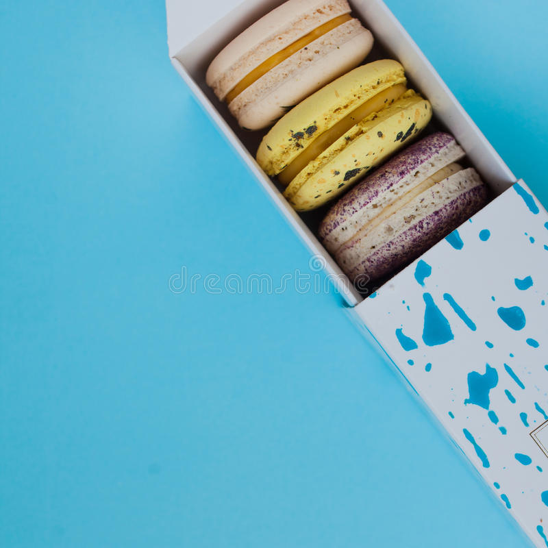 Lot of beautiful macarons. View from the top. In a box on a blue background. Lot of beautiful macarons. View from the top. In box on a blue background royalty free stock photography