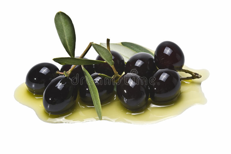 A lot of black olives on olive oil. A lot of black olives on some olive oil isolated on a white background royalty free stock photos