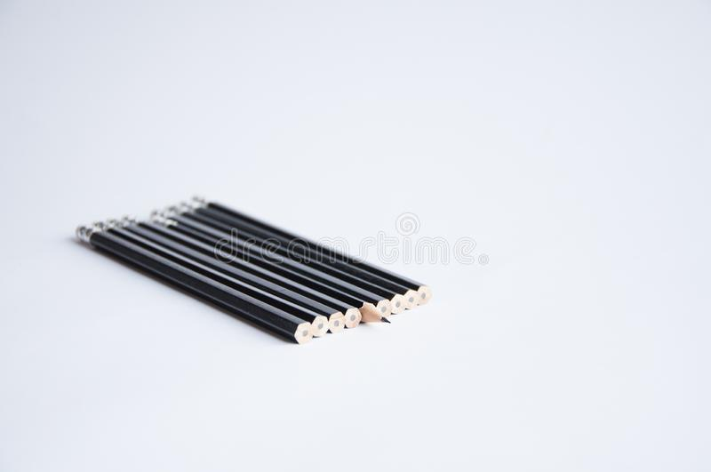 A lot of black pencils are on the white table. One pencil sharpened. stock images
