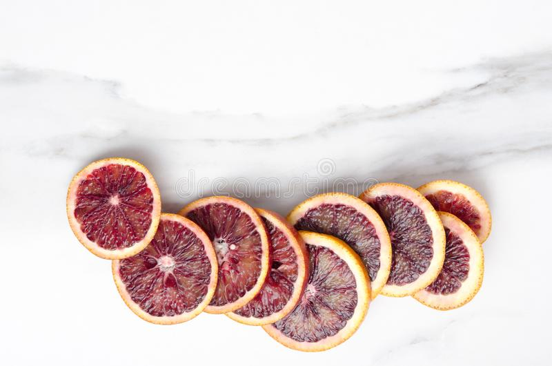 Lot of blood orange slices on the white marble table, top view. Empty space for your text stock photos