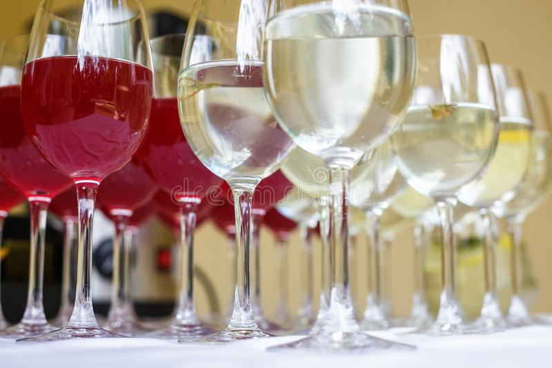 Lot of blurred glasses with red and white wine on the reception party table stock images