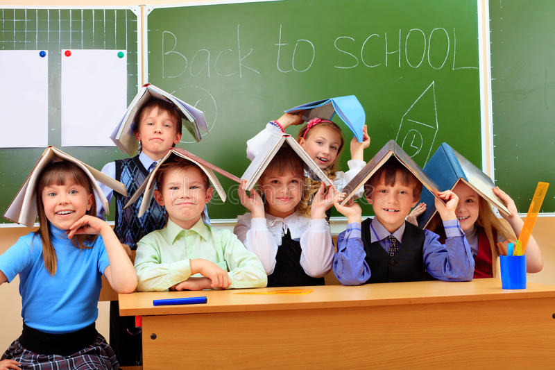 Lot of books. Happy schoolchildren at a classroom. Education stock photos
