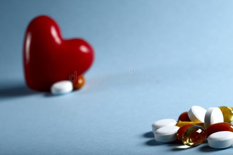 A lot of bright colored medicine pills and a red heart figure on a blue background. Cropped shot, horizontal, close-up, free space. Medicine concept. Crisis of stock photo