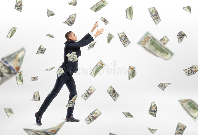 Lot of cash money flying and businessman catching them. A lot of cash money flying and a businessman catching them on the white background. Success aspiration royalty free stock photos