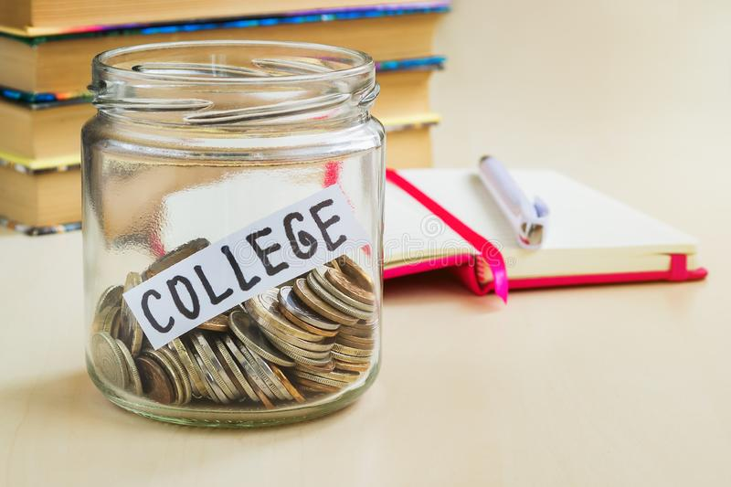 A lot of coins and college word in a glass jar near a white ballpoint pen and few books on a table. Saving money for college and royalty free stock photos
