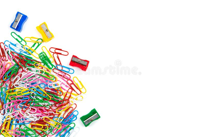 A lot of colored paper clips and pencil sharpeners on a white background. Top view and copy space royalty free stock photo
