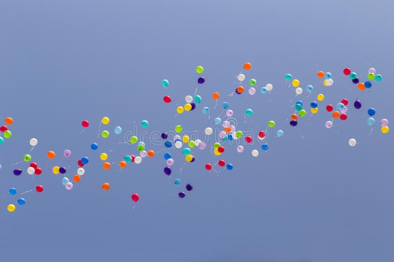 A lot of colorful balloons flying away in clear blue sky.  stock images