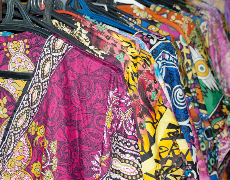 Lot of colorful dresses on hangers royalty free stock images