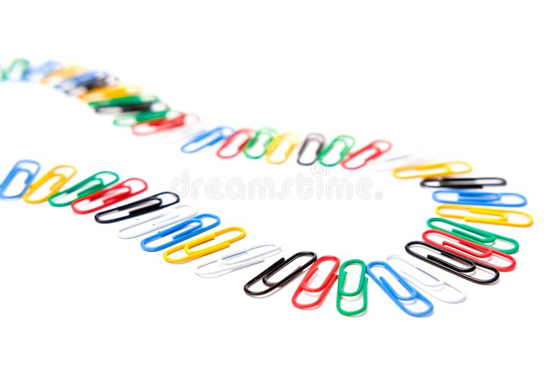 Colorful paper clips texture in white background. A lot of colorful paper clips in the floor with white background stock photo