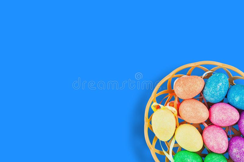Lot of colorful and sparkling artificial eggs in brown wicker basket on blue table. Copy space for your text. View from above. Hap. Py Easter celebration concept stock photo