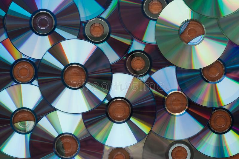 A lot of computer cd disks reflecting on a wooden surface, background, texture stock photography