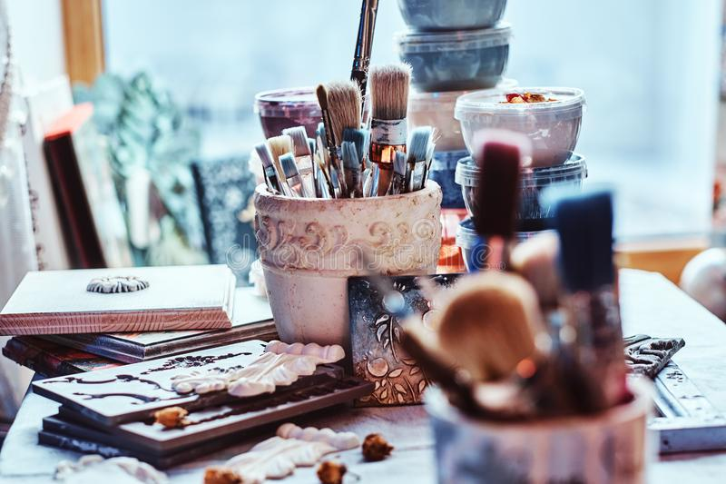 A lot of different brushes on artist`s table in jars. There are artistick`s mess on the table stock photos