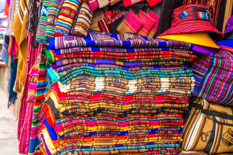 A lot of different colorful fabric coverlets on the souvenir store in Bolivia. A lot of different colorful fabric coverlets with patterns on the souvenir store stock photos