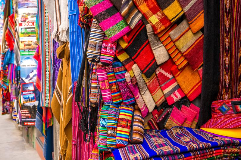 A lot of different colorful fabric coverlets on the souvenir store in Bolivia. A lot of different colorful fabric coverlets with patterns on the souvenir store stock photo