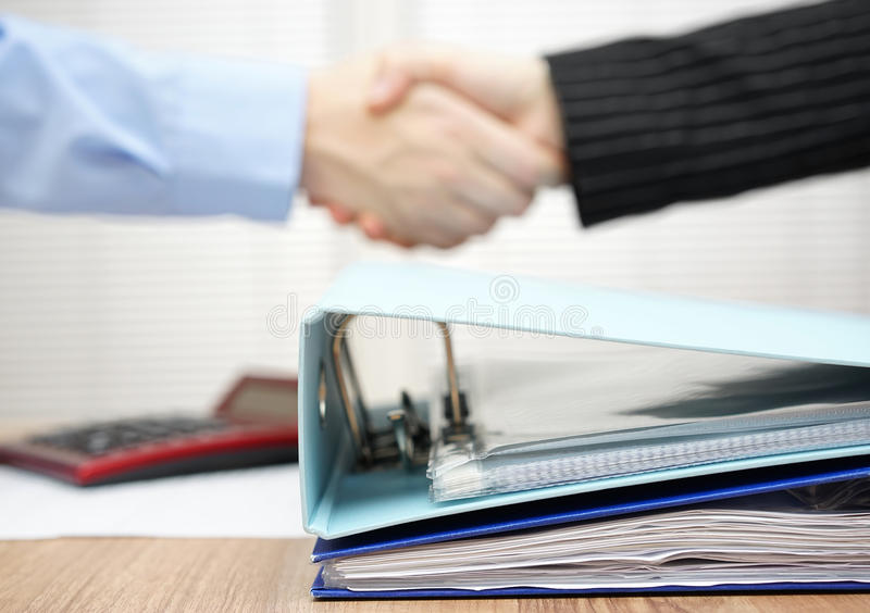 A lot of documentation in binder with handshake in blur.  stock photography