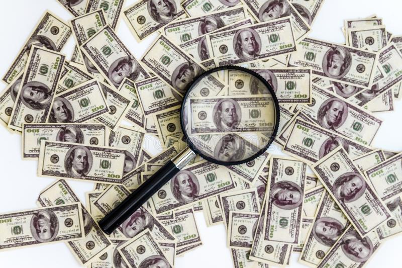 A lot of dollars banknotes on a white background and a magnifying glass on top, top view stock photos