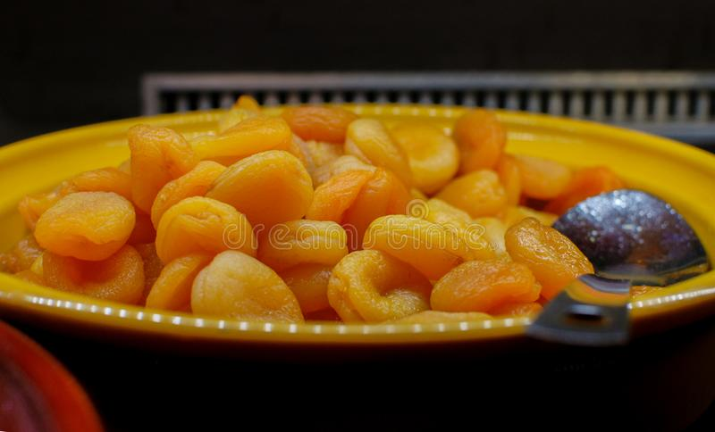 A lot of dried apricots in a bowl. On a dark background stock photo
