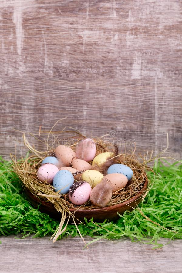 A lot of Easter quail eggs with feathers in a bird`s nest on natural green grass background. royalty free stock photo