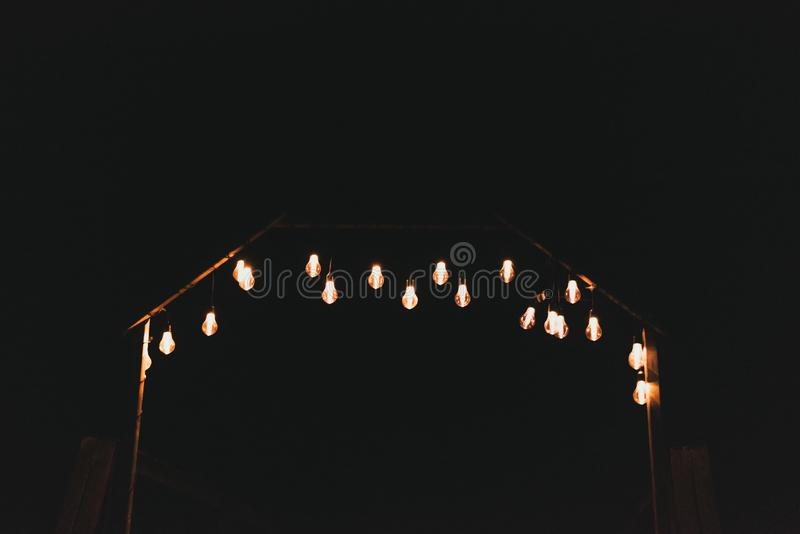 A lot of electric yellow light bulbs on the street at night. Bulbs on a garland outside in the dark. A lot of electric yellow light bulbs on the street at night royalty free stock photos