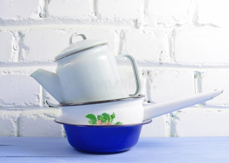 Lot of enameled dishes on a blue table against white brick wall background. Retro style cookware. Lot of enameled dishes on a blue table against white brick stock images