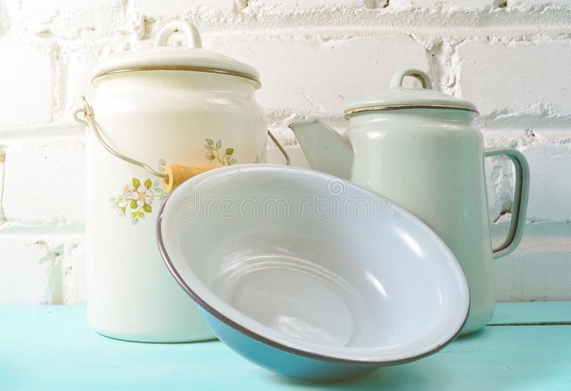 Lot of enameled dishes on a blue table against white brick wall background. Retro style cookware. Lot of enameled dishes on a blue table against white brick stock image