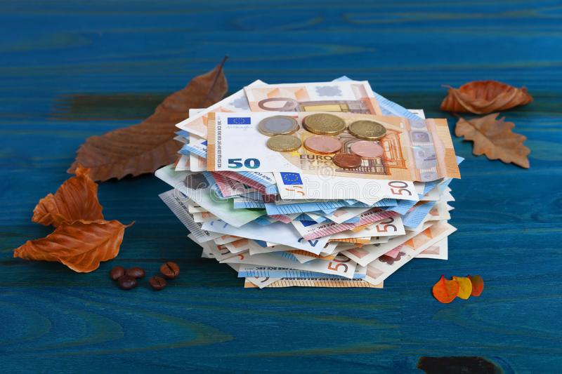 A lot of euro banknotes and coins with leaves and coffee beans on blue stock photos
