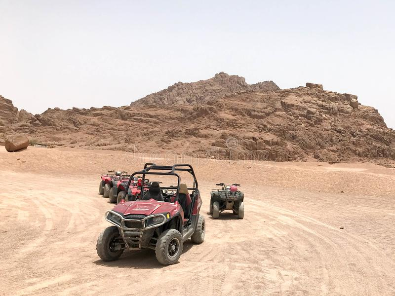 A lot of four-wheeled multicolored powerful fast off-road four-wheel drive buggies, cars, SUVs in the sandy hot desert on the sand stock image