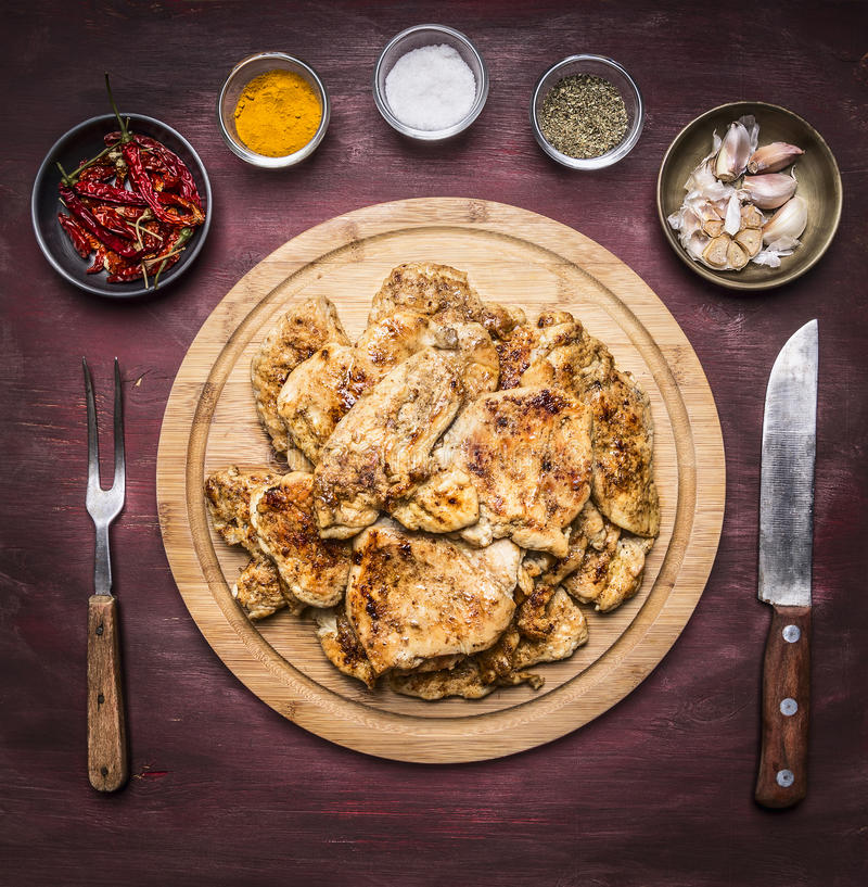 Lot of fried appetizing chicken steaks with herbs hot pepper and garlic with a fork knife on a round cutting board on rustic w stock photos
