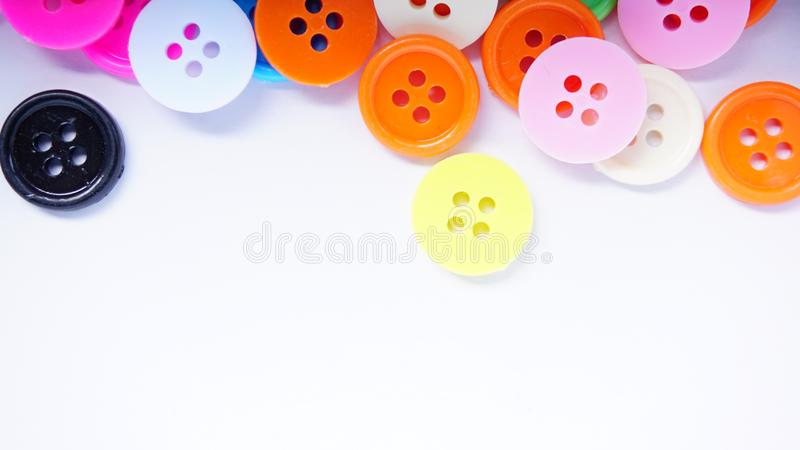 A lot of full spectrum multi colored vintage clothing plastic buttons randomly scattered on the white background - top view stock image