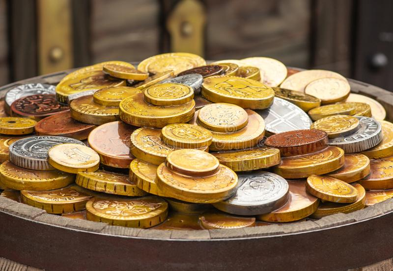 A lot of gold coins on a wooden barrel stock images