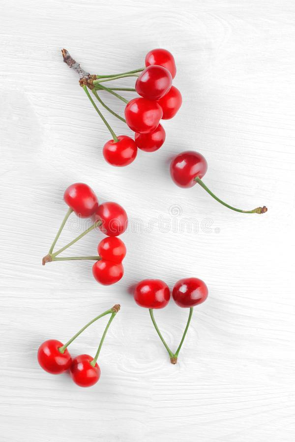 A lot of grubs of ripe, red, cherries on a white wooden background. top view stock photos