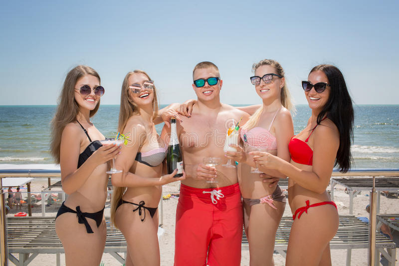 A lot of happy and cheerful people in swimming suits on a bright sea background. Summertime portrait of charming people stock image