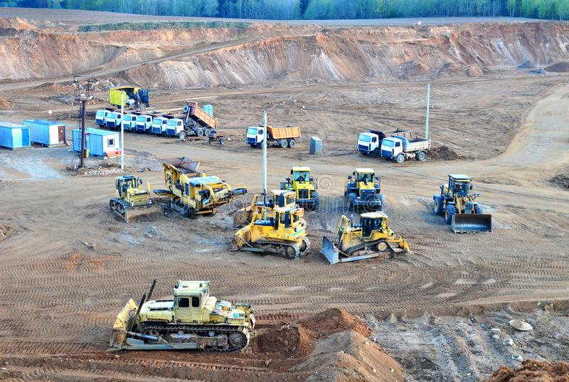 A lot of heavy construction equipment in the mining quarry. Parking with bulldozers, tractors, front loaders, excavators and dump royalty free stock image
