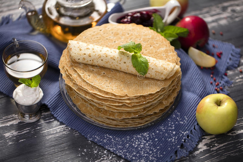A lot of homemade crepes. Homemade crepes on wood background with tea and sour cream and apple royalty free stock photography