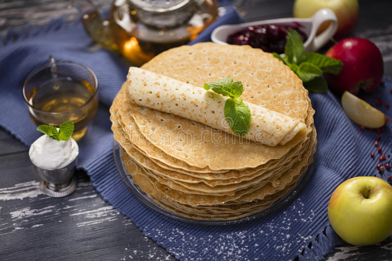 A lot of homemade crepes. Homemade crepes on wood background with tea and sour cream and apple royalty free stock photo