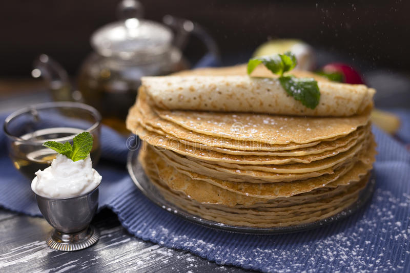 A lot of homemade crepes. Homemade crepes on wood background with tea and sour cream and apple royalty free stock photos