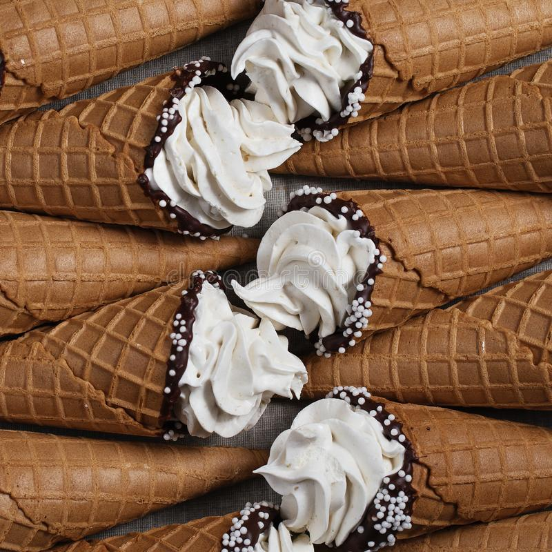 A lot of ice cream cones on wooden table. Soft ice creams or frozen custard in cones. Waffle marshmallows royalty free stock image