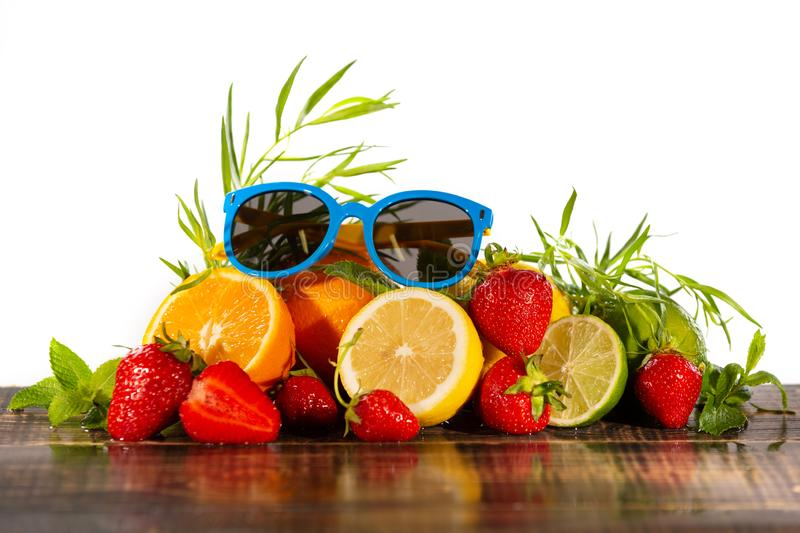A lot of juicy citrus fruits, strawberries and mint and tarragon, on wet wooden boards, sunglasses are on top, on a white. Background, with water drops, the royalty free stock image