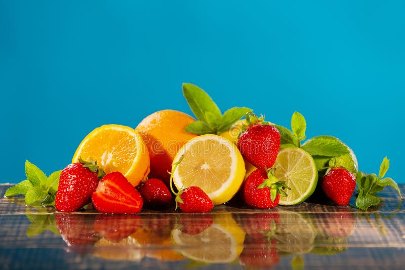 A lot of juicy citrus fruits, strawberries and mint on wet wooden boards, on a blue background, with water drops, the concept of stock image