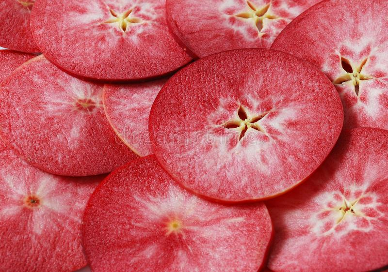 A lot of juicy slices of red apples stock photos