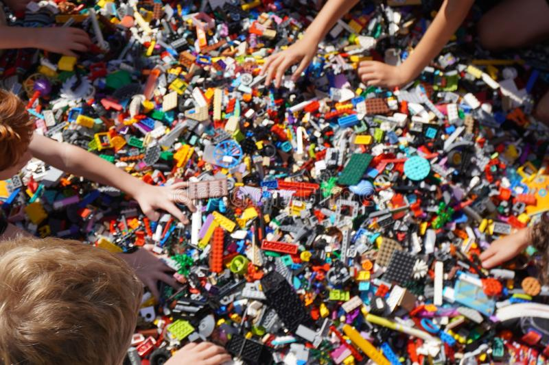 Kids hands reaching for lego blocks. A lot of kids grasping for lego`s at a party, many grasping hands for color things royalty free stock photography