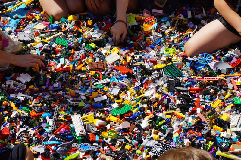 Kids hands reaching for lego blocks. A lot of kids grasping for lego`s at a party, many grasping hands for color things stock images