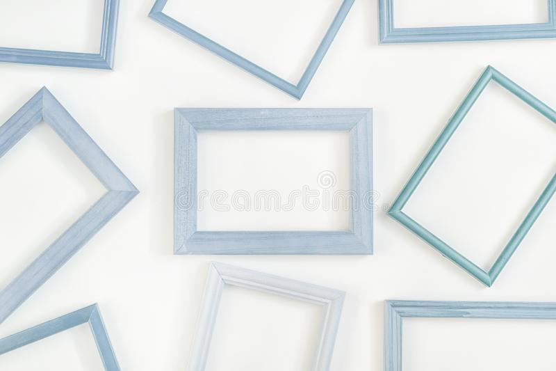 A lot of light blue empty frames are laid out on a white background. Space for text, layout. Unusual concept stock image