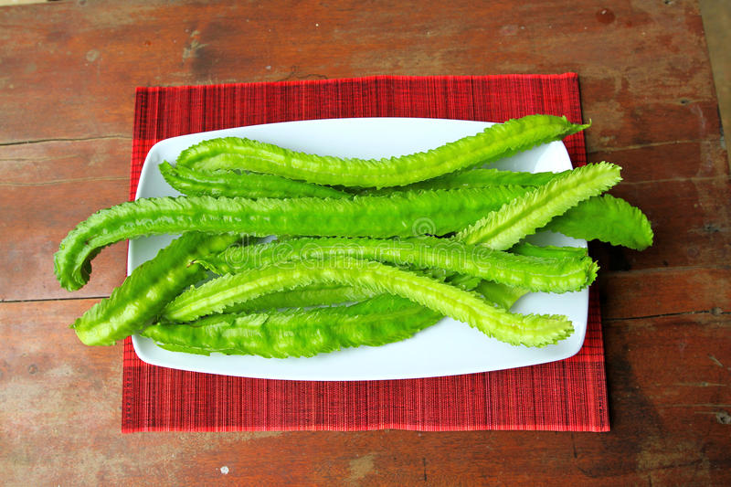 A lot of long winged beans Psophocarpus tetragonolobus. On wooden table and red mat stock image