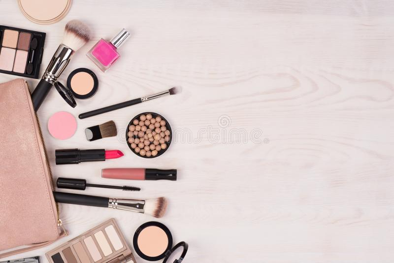 Makeup cosmetics and an open bag on white wooden background, top view with copy space stock images