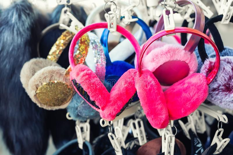 Lot of many multicolored bright fluffy fur earphones hanged on rack at store display for sale. Cute warm cold season clothes. Accessories, winter, muff, earmuff royalty free stock photography
