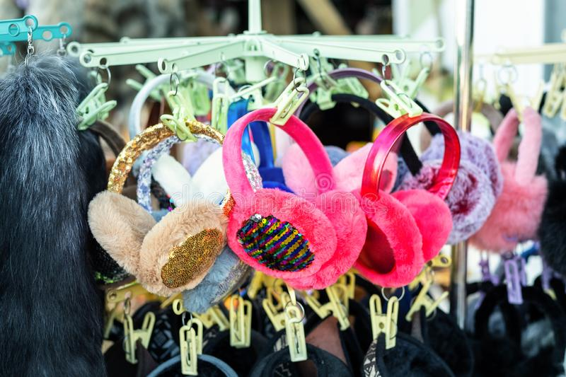 Lot of many multicolored bright fluffy warm winter fur earphones and gloves hanged on rack at store display for sale. Cute cold. Season clothes accessories stock photos