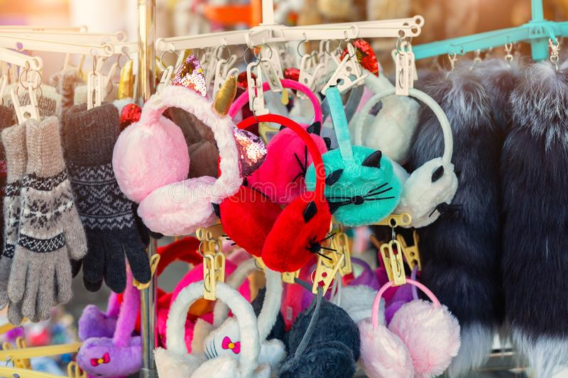 Lot of many multicolored bright fluffy warm winter fur earphones and gloves hanged on rack at store display for sale. Cute cold. Season clothes accessories royalty free stock photos